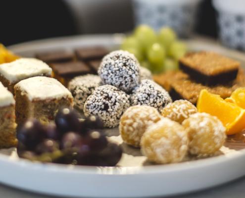 Närbild på fikafat med flera sorters frukt och kakor.