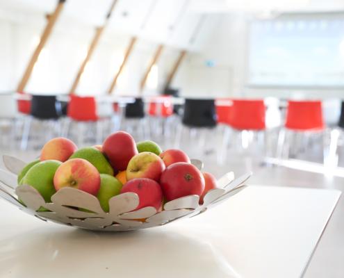 konferenslokal i bakgrunden med fruktskål på bord i fokus